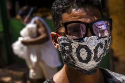 A youth wears a homemade face mask made of sequenced fabric amid the spread of the new coronavirus in Old Havana, Cuba.