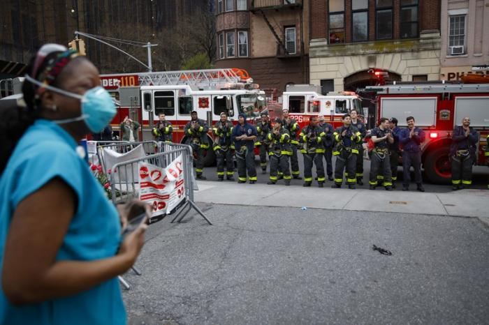 In this April 14, 2020, file photo FDNY firefighters gather to applaud medical workers as attending physician Mollie Williams, left, wears personal protective equipment due to COVID-19 concerns outside Brooklyn Hospital Center in New York
