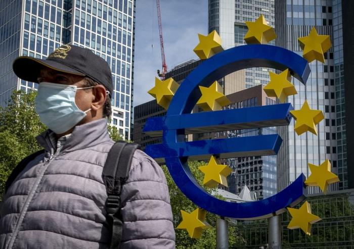 A man walks by the Euro sculpture in front of the old the European Central Bank in Frankfurt, Germany, Tuesday, May 5, 2020