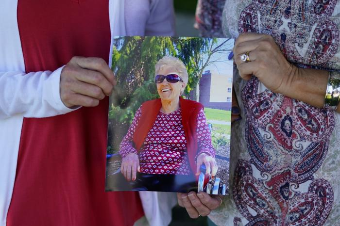 Angela Ermold, right, and her sister, Denise Gracely, hold a photo of their mother, Marian Rauenzahn, Thursday, June 17, 2021, in Fleetwood, Pa.
