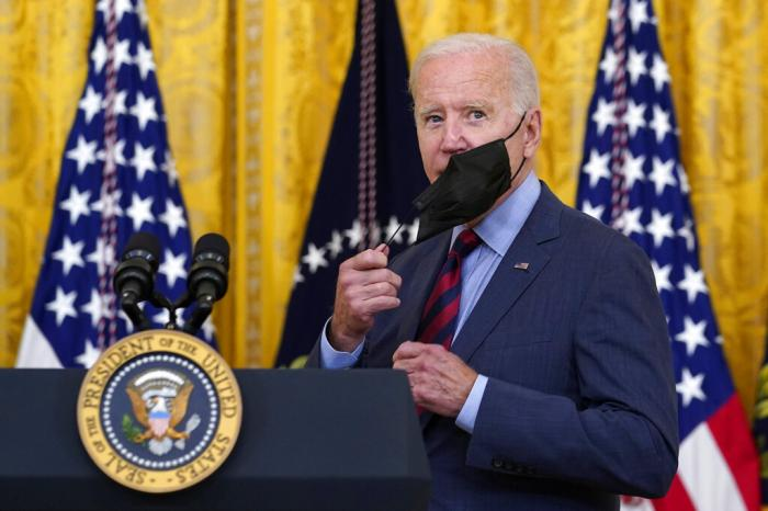 President Joe Biden takes off his mask as he arrives to speak about the coronavirus pandemic in the East Room of the White House in Washington, Tuesday, Aug. 3, 2021.