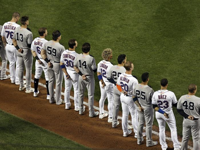 The New York Yankees and the New York Mets line up together along the baselines for the 20th anniversary of the 9/11 terrorist attacks before a baseball game on Saturday, Sept. 11, 2021, in New York